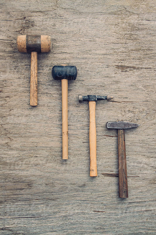 old rusty hammer on wooden background by Leander Nardin for Stocksy United