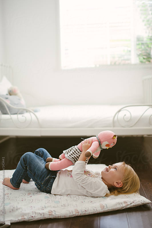 cute Toddler girl laying on floor in bedroom looking at doll by Kristin Rogers Photography for Stocksy United