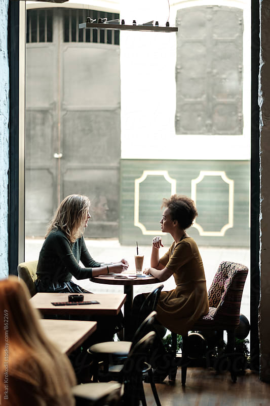 Two Friends Sitting at the Cafe by Branislav Jovanović for Stocksy United