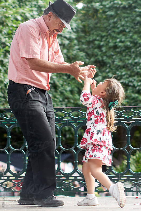 Grandpa and granddaughter dancing together by Per Swantesson for Stocksy United