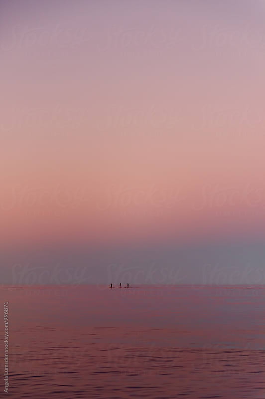 Three people stand up paddling after sunset by Angela Lumsden for Stocksy United