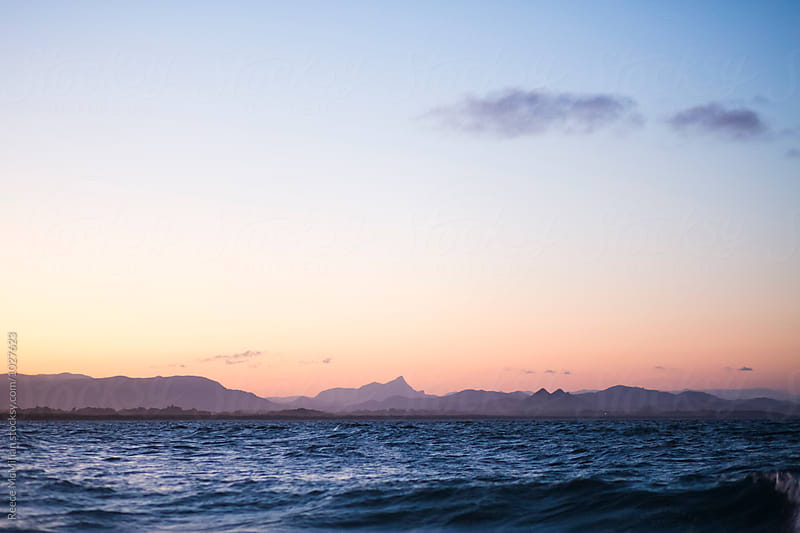 Byron Bay at sunset, Mount Warning in the background by Reece McMillan for Stocksy United