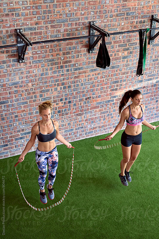 Muscular athletic girls using jump ropes for their workout in a gym by Daxiao Productions for Stocksy United