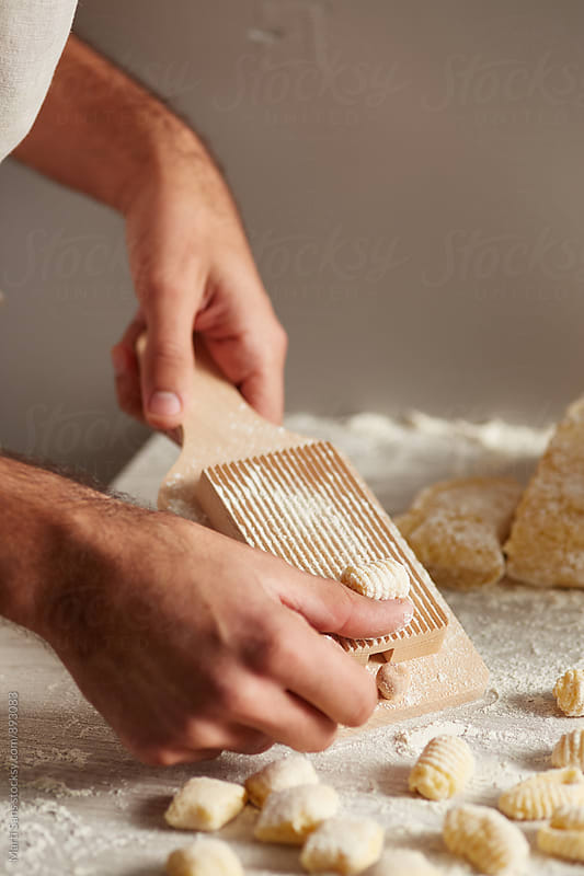 Close-up of man creating ridges on raw gnocchi by Martí Sans for Stocksy United