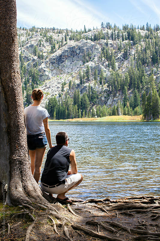 Father and daughter admiring the view at a lake in the Sierras by Carolyn Lagattuta for Stocksy United