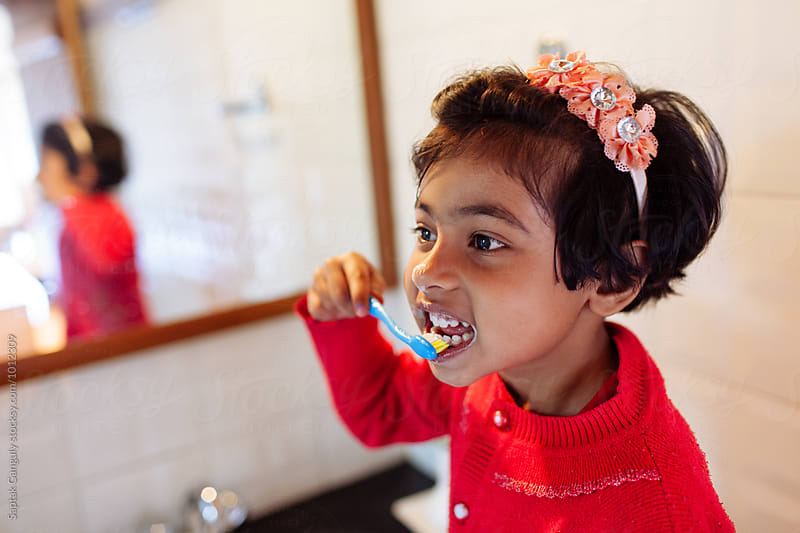 Little girl brushing her teeth  by Saptak Ganguly for Stocksy United