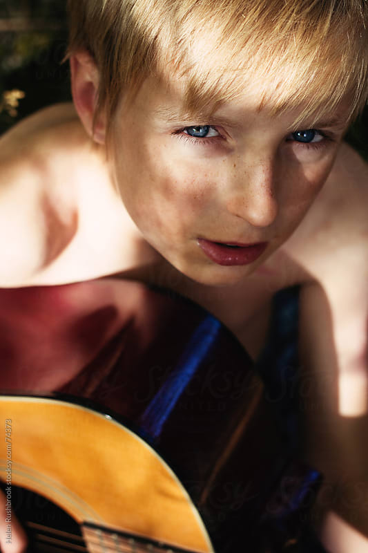 Pre-teen boy playing an acoustic guitar under a tree by Helen Rushbrook for Stocksy United