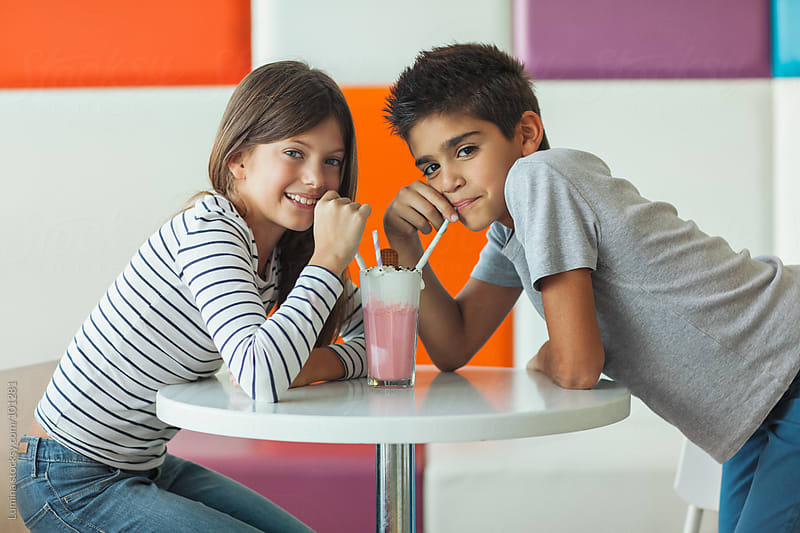 Boy and Girl Drinking Strawberry Milkshake by Lumina for Stocksy United