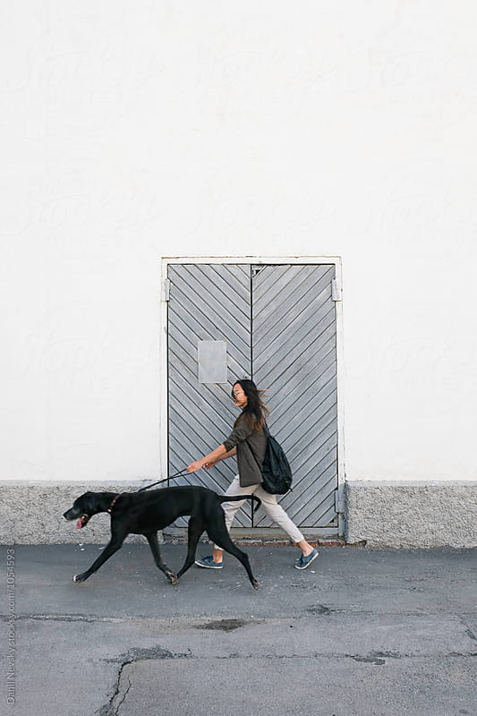 Side view of girl walking with big black dog by Danil Nevsky for Stocksy United