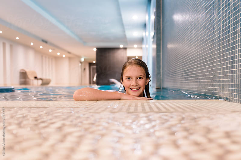 young girl in an indoor swimming pool by Gillian Vann for Stocksy United