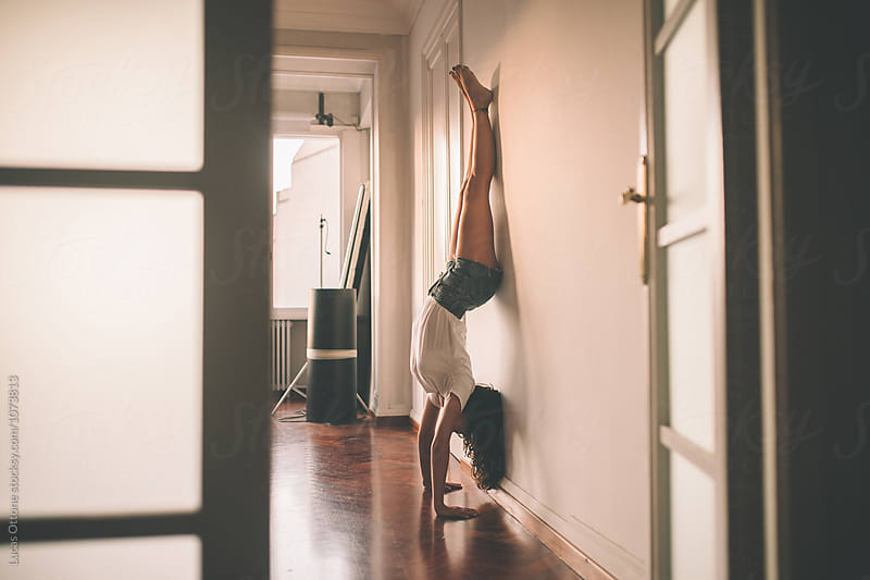 Young woman doing a headstand on a wall by Lucas Ottone for Stocksy United