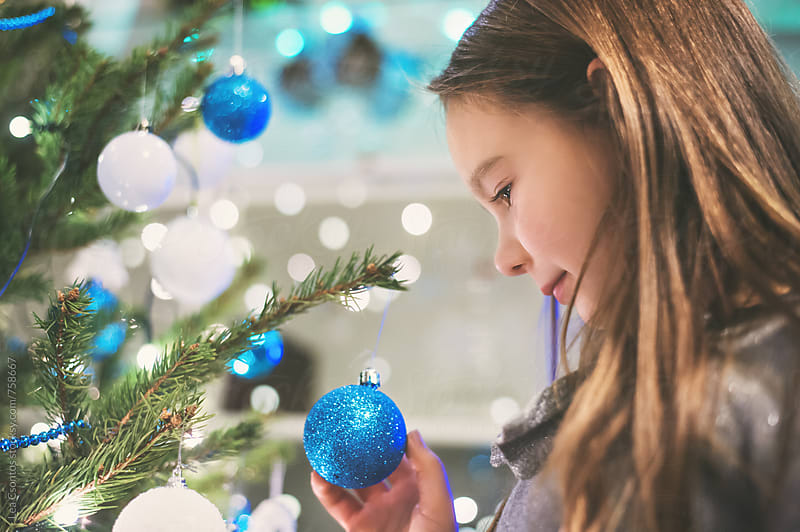 Young girl standing next to a christmas tree holding a bauble in her hand by Lea Csontos for Stocksy United