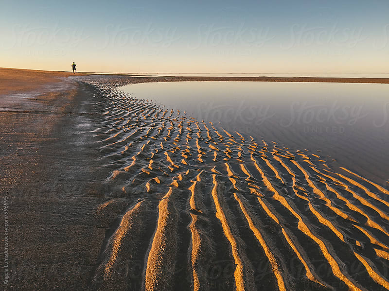 Solitary runner on the beach at sunset by Angela Lumsden for Stocksy United
