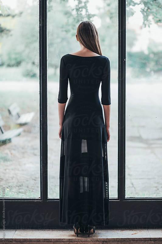 Beautiful woman in a dress standing near a window by Maja Topcagic for Stocksy United