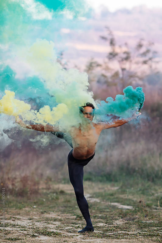 ballet dancer with two smoke bombs dance in nature by Igor Madjinca for Stocksy United