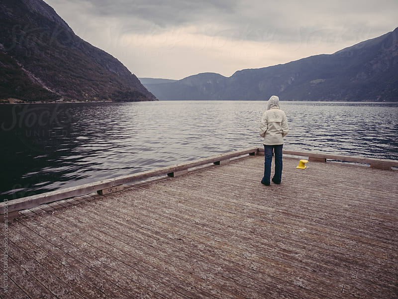 Woman Looking at a Fjord on a Rainy Evening by VICTOR TORRES for Stocksy United