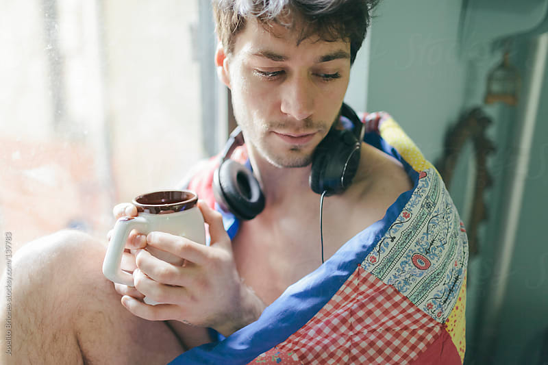 Young Man Waking Up in the Morning Listening to Music and Drinking Coffee by Window with Quilt by Joselito Briones for Stocksy United
