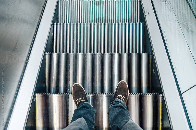 Feet of a man on escalator. POV horizontal shot by Alejandro Moreno de Carlos for Stocksy United