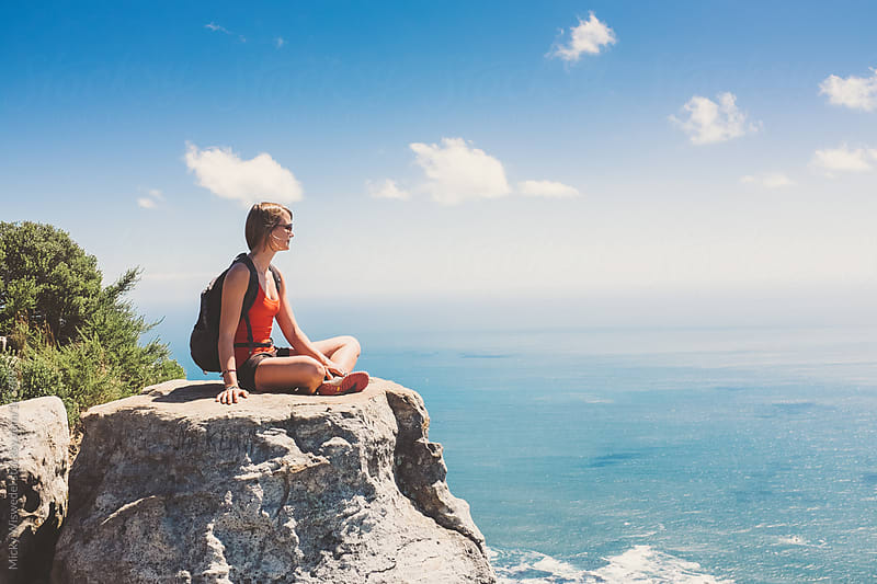 Fit young woman sitting on a rock overlooking the sea while hiking by Micky Wiswedel for Stocksy United
