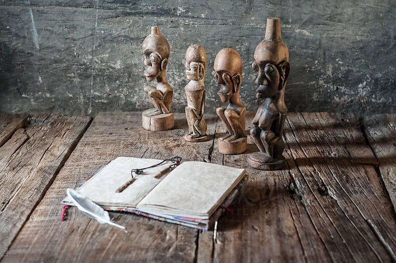 Wooden Figurines and a Religious Book by Lumina for Stocksy United