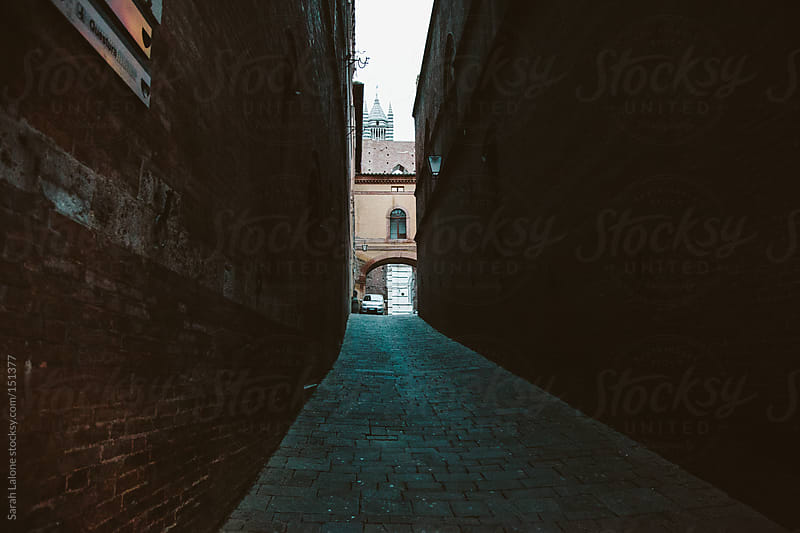 a dark alley in siena, italy by Sarah Lalone for Stocksy United