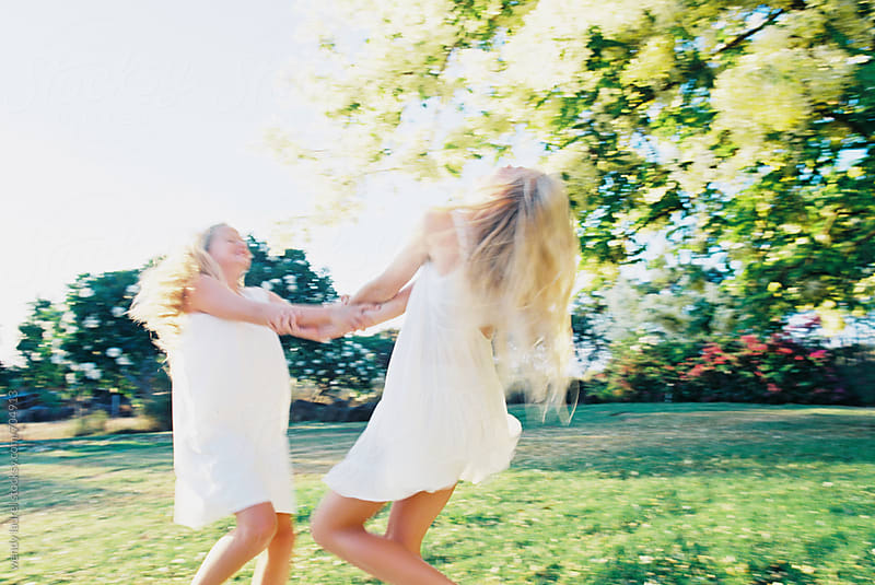 two girls in white dresses spinning under flowering tree by wendy laurel for Stocksy United