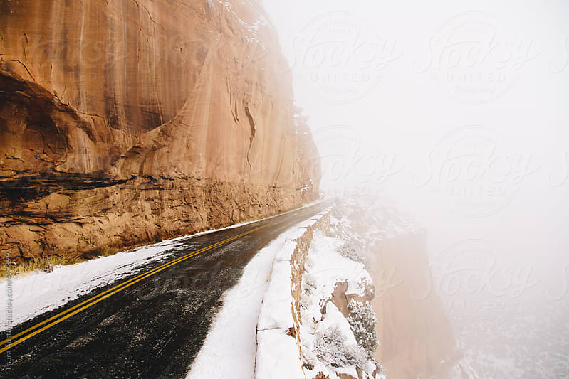Snow Covered Road Leading Into Fog by Laura Austin for Stocksy United