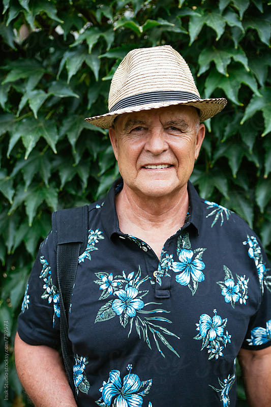 Stylish senior man smiling, wearing a straw hat and a hanbag, in front of plants by Inuk Studio for Stocksy United