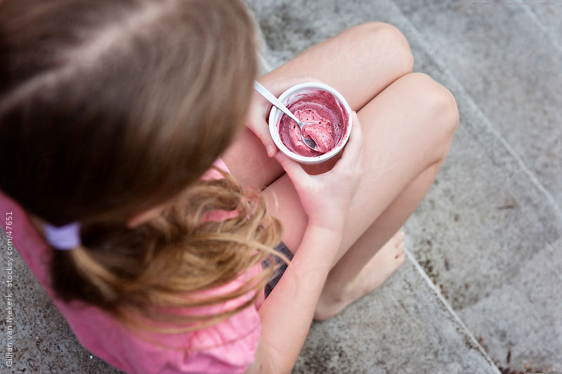 raspberry sorbet in little girl's hands by Gillian Vann for Stocksy United