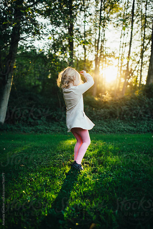 A little girl twirls in the light of the setting sun by Amanda Voelker for Stocksy United