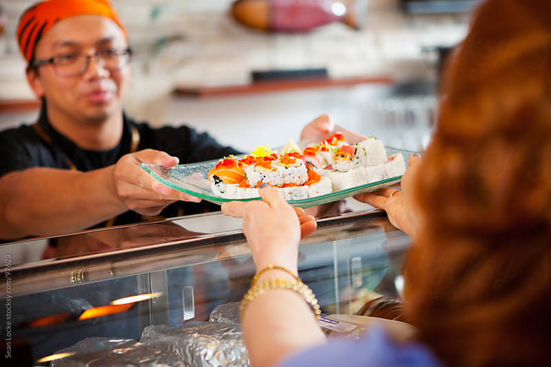 Sushi: Woman Gets Plate of Sushi from Chef by Sean Locke for Stocksy United