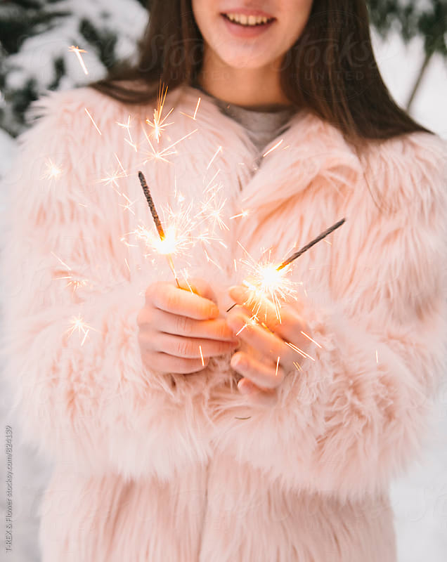 Close-up of woman's hands holding sparklers by T-REX & Flower for Stocksy United