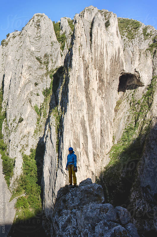 Woman standing on top of a narrow rocky ridge by RG&B Images for Stocksy United