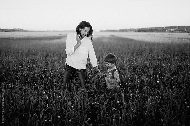 Mother and boy walking in the field by Evgenij Yulkin for Stocksy United