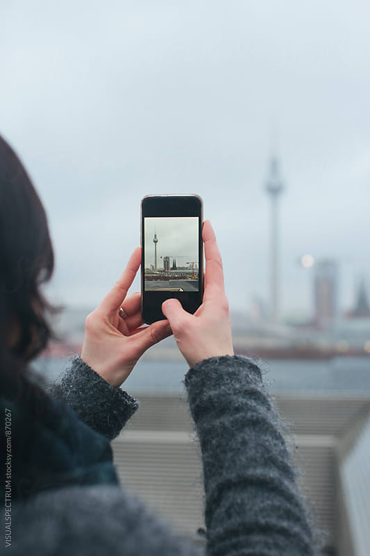 Detail of Woman Taking Smartphone Photo of Berlin's TV Tower on Rainy Winter Day by VISUALSPECTRUM for Stocksy United