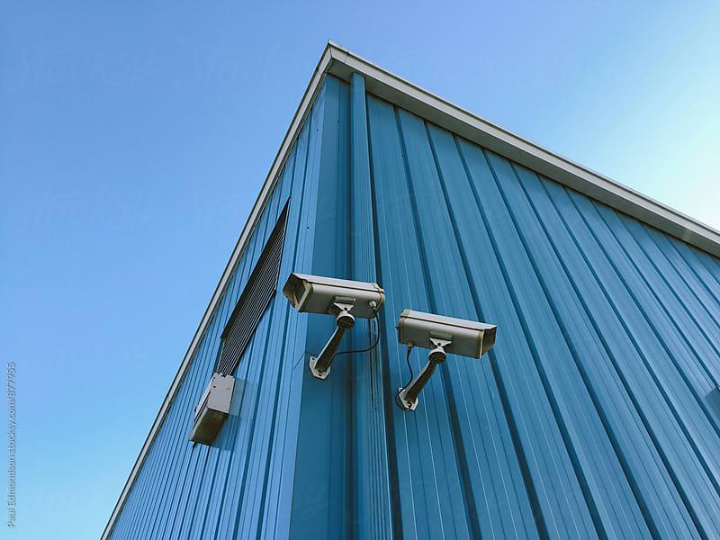Surveillance cameras on building exterior by Paul Edmondson for Stocksy United