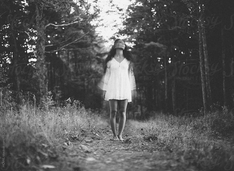 Lone woman stands alone in forest, blurry abstract face by HOWL for Stocksy United