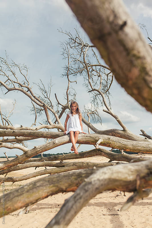 Barefoot little girl in white dress sitting on tree branches by Cindy Prins for Stocksy United