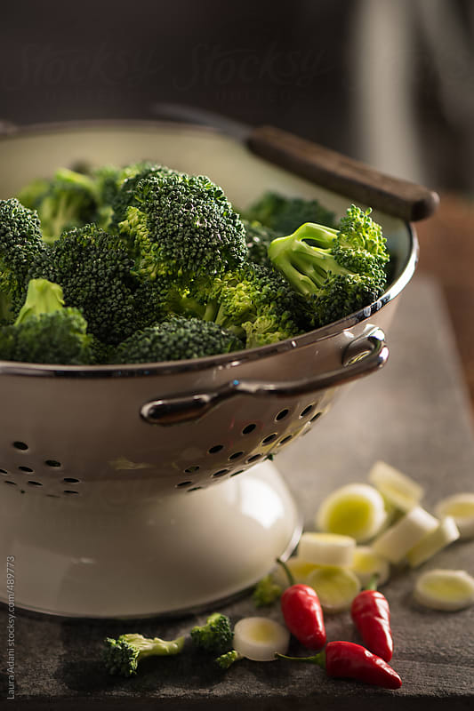 floret of broccoli in a colander by Laura Adani for Stocksy United