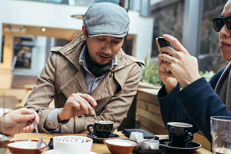 Two Good-Looking Young Asian Men Having Coffee in Bright Café by VISUALSPECTRUM for Stocksy United
