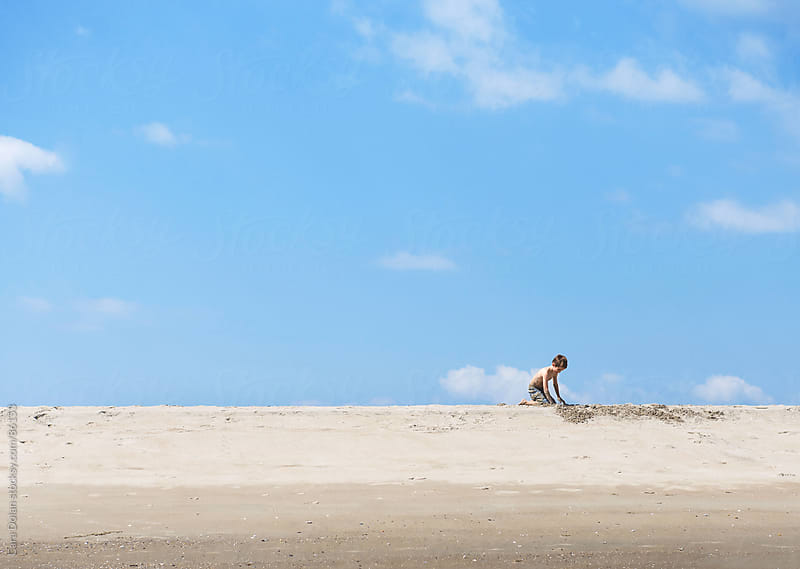 Boy plays in the sand on a beach under a blue sky by Cara Dolan for Stocksy United