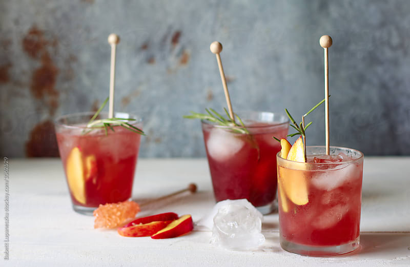 Peach and blood orange cocktail with rosemary by Babett Lupaneszku for Stocksy United