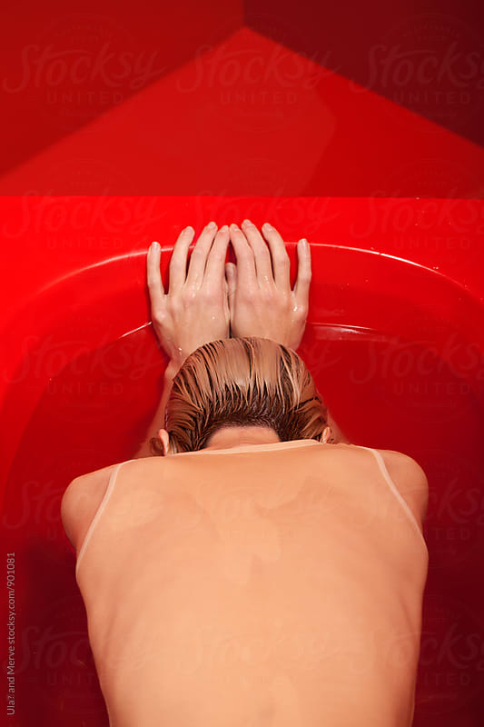conceptual image of a young blond woman wearing a body suit  in a red bathtub by Ulaş and Merve for Stocksy United