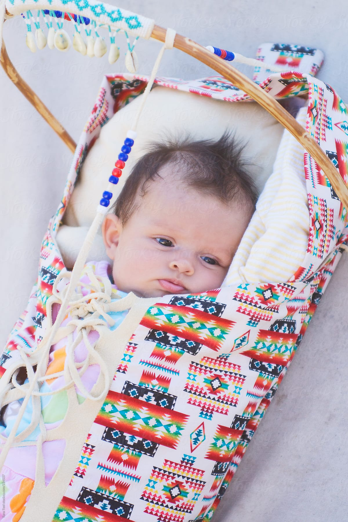 A Native American baby wrapped securely in a papoose by Tana Teel ...