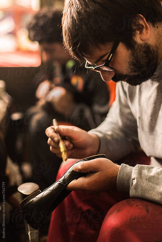 Cobbler repairing old shoes. by Audrey Shtecinjo for Stocksy United