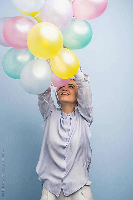 Cheerful girl holding colorful balloons by T-REX & Flower for Stocksy United