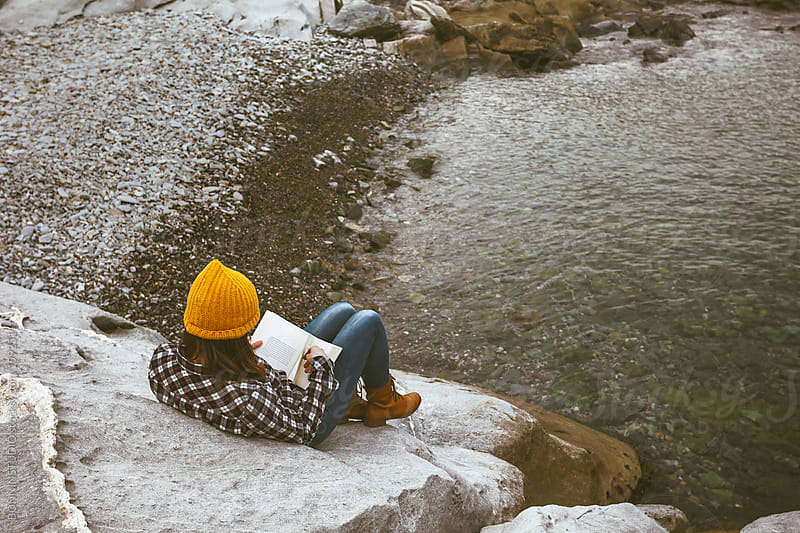 Young woman reading a book on the rock at seashore. by BONNINSTUDIO for Stocksy United