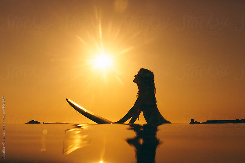 young woman surfer with surfboard silhouetted in water at golden hour by Jonathan Caramanus for Stocksy United