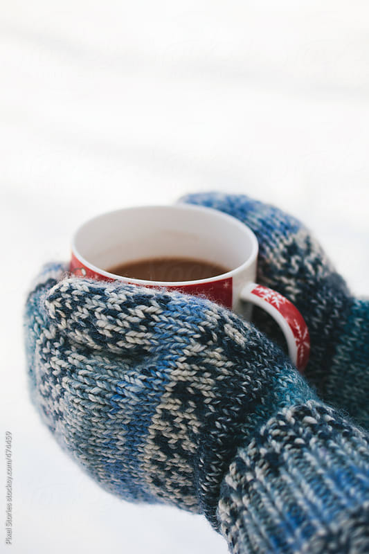 Hands with blue mittens holding Christmas-theme cup with hot cocoa by Pixel Stories for Stocksy United