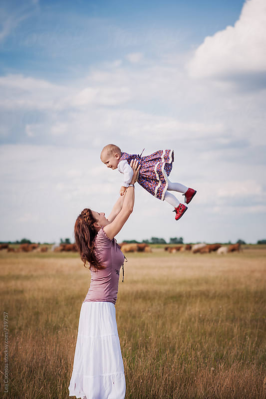 Mother lifting her baby in the air on a beautiful field by Lea Csontos for Stocksy United
